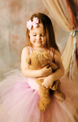Little ballerina beauty hugging teddy bear