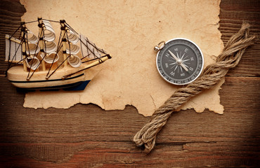 old paper, compass, rope and model classic boat on wood backgrou