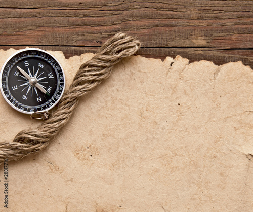 old paper, compass and rope on wood background