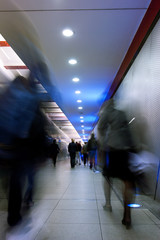 Motion blurred people in a metro tunnel