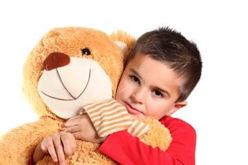 bambino abbraccia il suo grande orsacchiotto