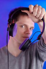 Mann hält Kopfhörer
