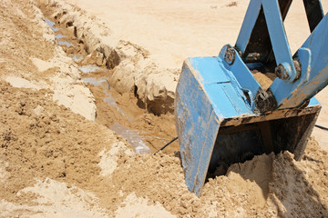 The dredge digs a trench in sand