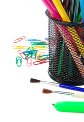 paintbrush, paper clips and pencil in holder on white