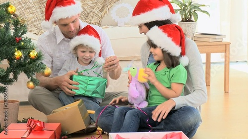 Lovely family opening Christmas gifts