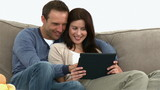 Happy couple using a computer tablet sitting on the couch