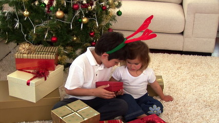 Montage of two children opening their present