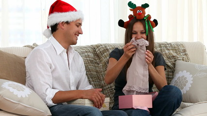 Woman opening a gift that was offered by her husband