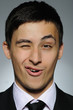 Portrait of funny young business man winking. expressions on gra