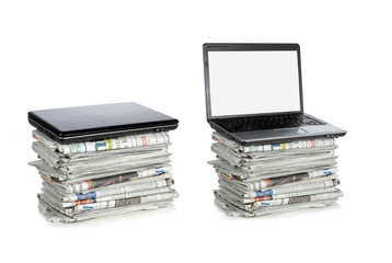 newspaper and laptop over white background