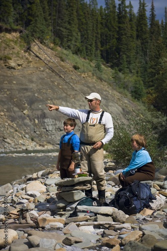 Father And Sons On River Shoreline