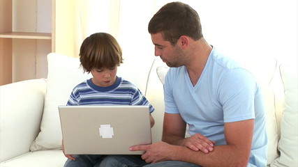 Concentrated father explaining his son how to use a laptop