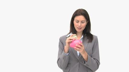 Happy businesswoman saving money in a piggybank