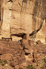 Hiker explores an ancient Anasazi cliff-dwelling.