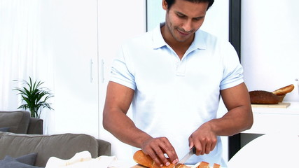 Handsome man cutting bread