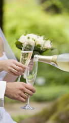Somebody fills newly-married couple's glasses with champagne
