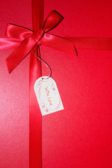 Red ribbon on red background with love note