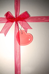 Red ribbon on silver background with heart