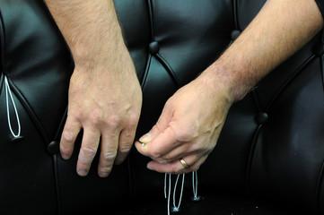 mani che lavorano un divano