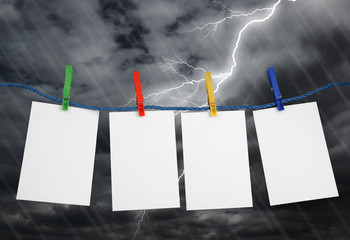 Pieces of paper and colored clothespins on sky background