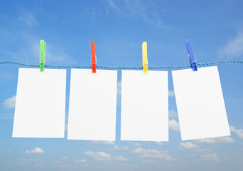 Blank pieces of paper and colored clothespins on sky background