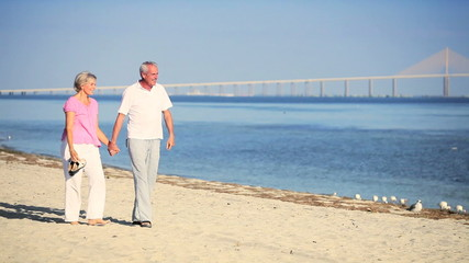 Healthy Contented Mature Couple Walking the Beach