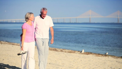 Contented Seniors Walking the Beach
