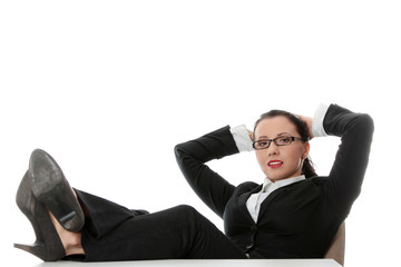 Young businesswoman relaxing at the desk, legs up