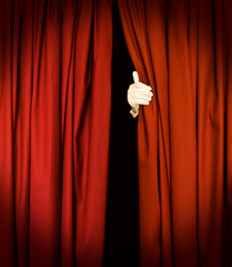 Magician behind red curtains