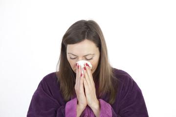 Frau niest in ein Taschentuch