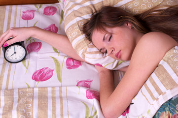 Woman sleep in bed with alarm in the hand
