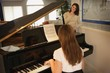Teenage Daughter Playing The Piano For Her Mother