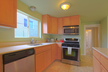 Green kitchen with maple cabinets and black appliances