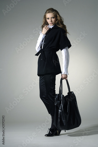 Fashion girl with bag posing in the studio