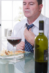 man arranging the necktie at restaurant with red wine