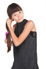 Young brunette teenager combing long hairs on white