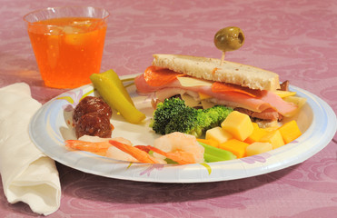 Plate of party foods - cold cuts, sandwich, veggies, and drink