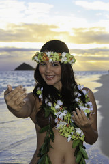 woman dancing hula by the ocean in hawaii