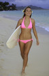 blond girl in pink bikini with surfboard on a hawaii beach