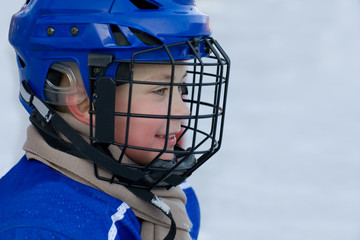 Boy plays hockey on the outdoor ice area. Boy 7 years.