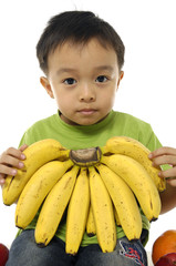 Close up little boy holding banana