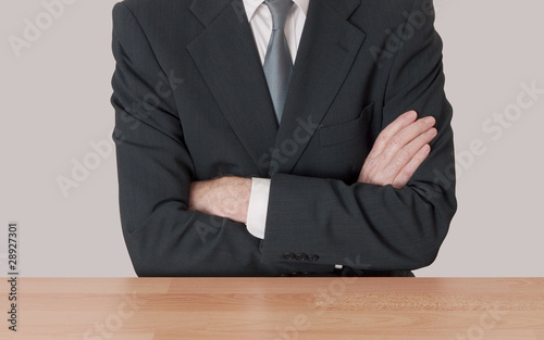 Inaction concept - man at desk with arms crossed