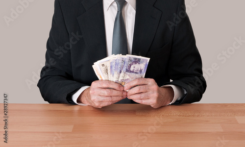 Man in suit sitting with cash - pounds sterling