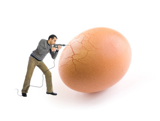 Young man cracking an egg using a drill tool