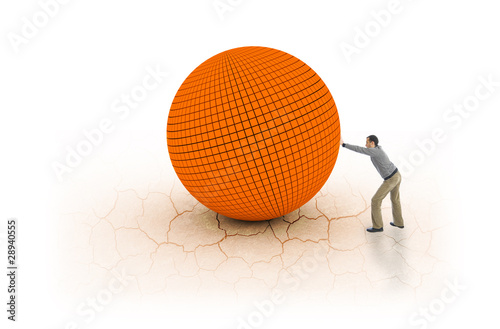 Young man pushing big and heavy ball on cracked earh