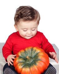 Beautiful blond baby with a big pumpkin