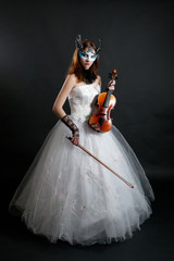 Girl in white dress and mask with violin
