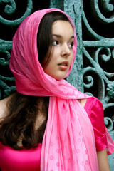Young caucasian woman in pink near the gates
