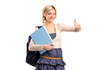 Female student with a school bag holding a book and giving thumb