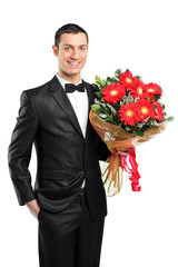 A man holding out large bouquet of gerberas